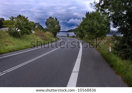 bending road winding through nature - stock photo
