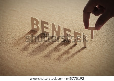 BENEFIT wood word on compressed or corkboard with human's finger at T letter.