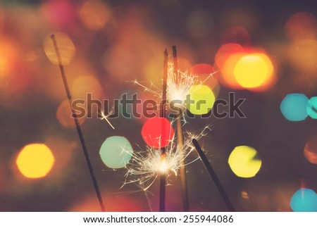 Bengal fire, sparkler and colorful bokeh christmas, new year background. - stock photo