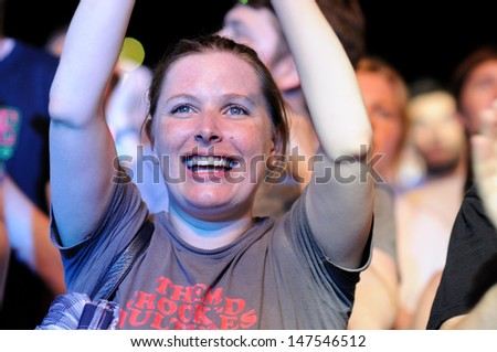 BENICASIM, SPAIN - JULY 18: A woman from the audience watches a concert at FIB (Festival Internacional de Benicassim) 2013 Festival on July 18, 2013 in Benicasim, Spain. - stock photo