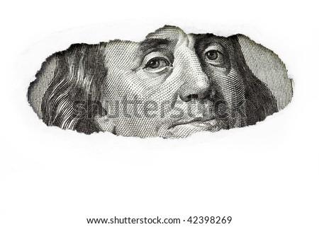 Benjamin Franklin macro peeking through torn white paper. - stock photo