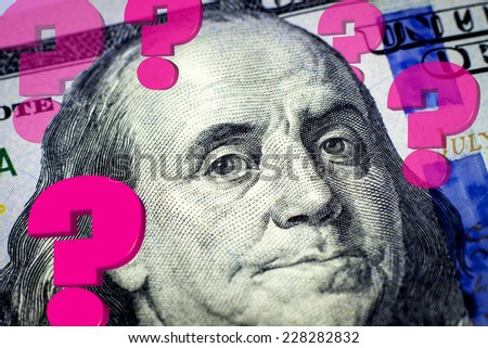 Benjamin Franklin's portrait and question marks expressing financial uncertainty - Financial concept - stock photo