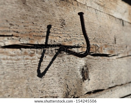 bent nail into a wooden wall - stock photo