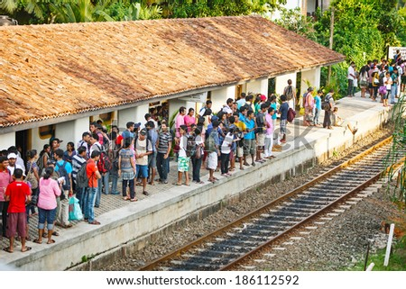 BENTOTA, SRI LANKA - 28 APR 2013: People wait for a train on railway platform in Bentota, Sri Lanka. Trains are becoming more popular transport last years due to railway improvement by government. - stock photo