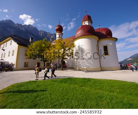 BERCHTESGADEN, GERMANY - SEPTEMBER 17, 2011: tourists visiting St. Bartholomew's Church, Berchtesgaden. photo of an autumn day in Bavarian Alps taken on September 17, 2011 at St. Bartholomew's Church. - stock photo