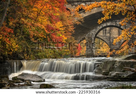 Berea Falls during peak fall colors. This cascading waterfall looks it's best with peak autumn colors in the trees. You can see the stone arch train bridges in the background crossing the Rocky River. - stock photo