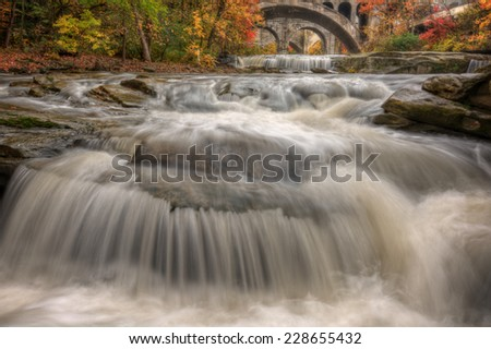 Berea Falls Ohio during peak fall colors. This cascading waterfall looks it's best with peak autumn colors in the trees. The stone arch train bridges make for a nice background. - stock photo