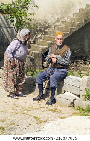 BEREKET, TURKEY - APRIL 10: Unidentified elder couple in traditional rural dress enjoy a rest in the spring sun in a small village near Antalya, on April 10, in Bereket, Turkey