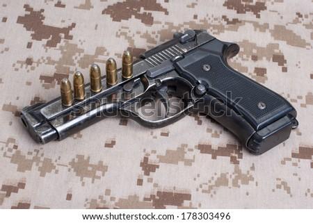 Beretta hand gun on  desert marines uniform - stock photo