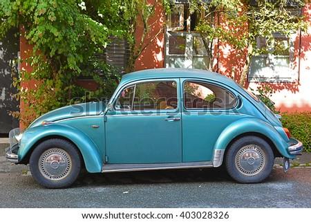 BERGEN,NORWAY - AUGUST 22, 2014 : Volkswagen Beetle parked on a quiet street in the city of Bergen. - stock photo