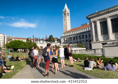 BERKELEY, CA- Apr 16, 2016: Students at the University of California Berkeley campus enjoying a warm spring day outdoors on the grass. The Campanile tower is seen in the background. - stock photo