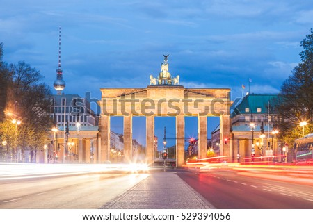 Berlin Brandenburg gate at night, long exposure with traffic lights trails. Berlin tv tower on background. View from the west side of Berlin. German name is Brandenburger Tor