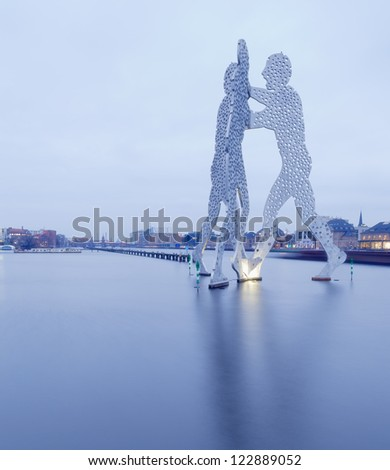 BERLIN - CIRCA 2011: Molecule Man designed by Jonathan Borofsky, on CIRCA 2011 in Berlin, Germany. Symbol of the unity of the three restructured in the 2001 district Treptow and Friedrichshain - stock photo
