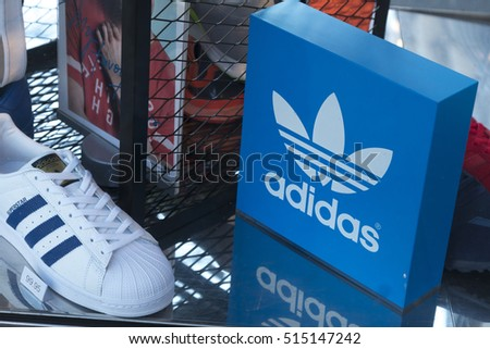 Berlin, Germany - April 26, 2016: Adidas logo and shoes in shop window. Adidas AG is a German multinational corporation that designs and manufactures sports shoes and clothing headquartered in Bavaria