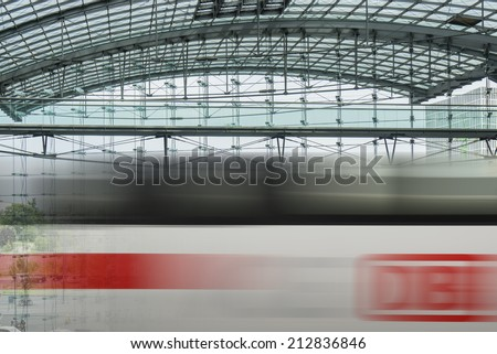 BERLIN, GERMANY- AUGUST 10, 2013: Passing ICE train with brand of the Deutsche Bahn at the main train station of Berlin, Hauptbahnhof - stock photo
