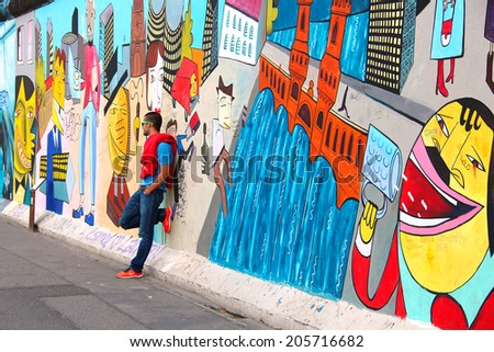 BERLIN, GERMANY - JULY 2, 2014: People taking pictures at the East Side Gallery exhibition, the largest outdoor art gallery in the world, painted on the segment of Berlin wall - stock photo