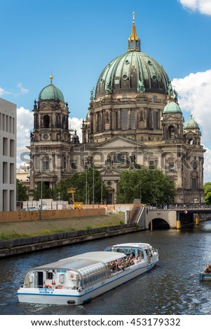 BERLIN, GERMANY - JULY 03, 2016: View of Berlin Cathedral (Berliner Dom) at Museum Island with excursion boat on Spree river in summer. The construction site of the Kaiser's Palace on the left.