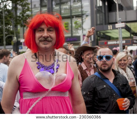 BERLIN, GERMANY - JUNE 21, 2014: Christopher Street Day. Crowd of people Participate in the parade celebrates gays, lesbians,  and transgenders. Prominent in the image, elaborately dressed transgender