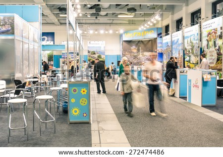 BERLIN, GERMANY - MARCH 8, 2014: attendees and expositors in Ukraine area at ITB Travel Trade Show in the fairgrounds of Messe Berlin. Blurred motion on people due to long exposure. - stock photo