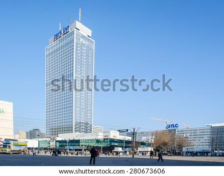 BERLIN, GERMANY, MARCH 12, 2015: people are strolling over the famous alexanderplatz in berlin which used to be in the eastern germany and now it is famous for world clock and fernsehturm views.