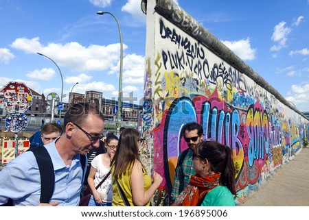 BERLIN, GERMANY-MAY 31, 2014: people walk by the western wall that separated western and eastern Germany for 28 years, in Berlin. - stock photo