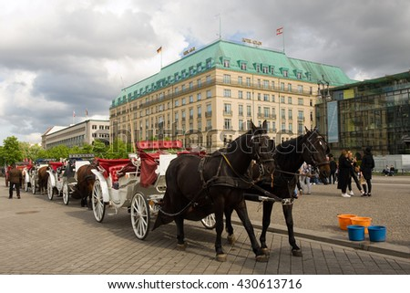 Berlin, Germany- May 15, 2016: View on Hotel Adlon Kempinski on Pariser Platz an Horses in the foreground. Berlin. At the corner with Pariser Platz, directly opposite site the Brandenburg Gate