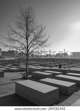 BERLIN, GERMANY - NOV 12: An unidentified tourist visits the Holocaust Memorial on November 12, 2011 in Berlin, Germany. The memorial was dedicated in May 2005 with 2,711 concrete blocks in this area. - stock photo