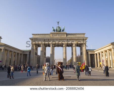 BERLIN, GERMANY - NOV 12: Unidentified young men dress as a bear, Russian and german soldiers stand as a tourist attraction in front the Brandenburg gate on November 12, 2011 in Berlin, Germany. - stock photo