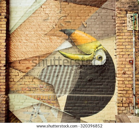 BERLIN, GERMANY - SEP 4: Tropic bird on colorful graffiti artwork on brick wall on September 4, 2015. Urban area of Berlin comprised about 4 million people making it the 7th most populous in EU - stock photo