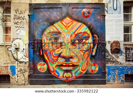 BERLIN, GERMANY - SEPT 2, 2015: Graffiti with beautiful face of ethnic lady on the rustic door of garage on Septemper 2, 2015. Urban area of Berlin comprised 4 million people, 7th most populous in EU - stock photo