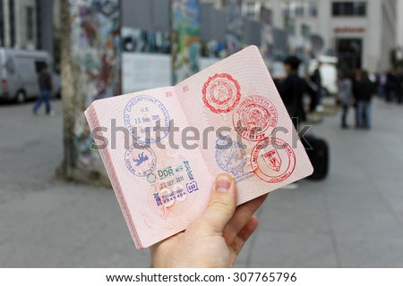 BERLIN, GERMANY - SEPTEMBER 22, 2011: Man holding open passport with stamps of the Cold War at the background of fragments of the Berlin Wall. - stock photo