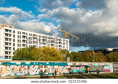 BERLIN, GERMANY - SEPTEMBER 28, 2015:  Modern building at the East Side Gallery in Berlin, Germany. The East Side Gallery is the longest preserved stretch of the Berlin wall and was painted by artists - stock photo