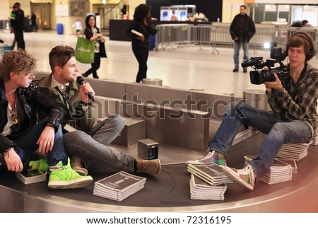 BERLIN - JANUARY 21: Designer interviews on conveyor belt at Bread & Butter fair on January 21, 2011 in Berlin, Germany. Tens of thousands of visitors come each year.