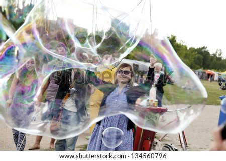 BERLIN - JUNE 10: A group of young adults making giant soap bubbles on an early summer day at Mauerpark, with the flea market in the backgroundon June 10 2012 in Berlin, Germany.