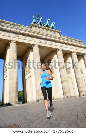 Berlin lifestyle. Running woman in Berlin, Germany by Brandenburg Gate jogging living healthy lifestyle. Female runner jogging. Urban fitness girl working out outdoors in jacket. - stock photo