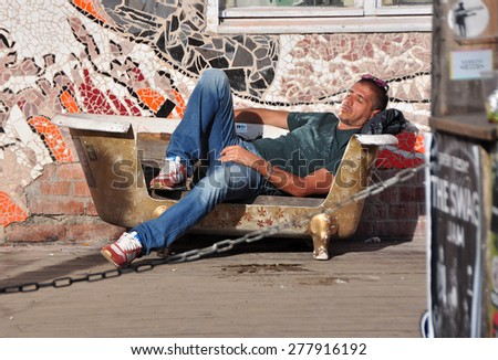 BERLIN â?? March 1st: Unidentified man resting on the Flowmarkt  (flea market). Taking place from April till October on every first and third Sunday on March 1 2015 in Berlin, Germany. - stock photo