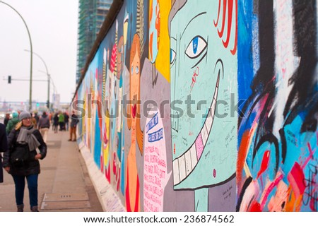 BERLIN - NOV 15, 2014: Unidentified people walking and looking at the Berlin Wall at East Side Gallery.  - stock photo