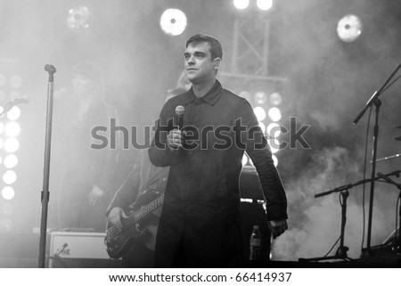 BERLIN - OCTOBER 23: Robbie Williams performs at his surprise concert in front of the Max-Schmeling-Halle in Berlin. October 23, 2009 in Berlin, Germany - stock photo