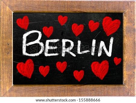 Berlin written on a used blackboard and surrounded by chalk drawings of heart shapes - stock photo