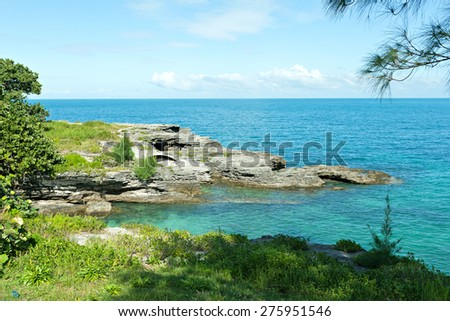 Bermuda coast with aqua blue tropical waters and rock formations complete with small caves. - stock photo