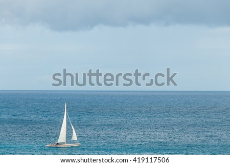 Bermuda rigged yachting sloop in the Caribbean on a cloudy day