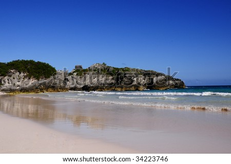 Bermuda's Horseshoe Bay beach during a hot summer day.  Photo includes the sky, large rocks along the coastline, pink sand and the tide rolling in. - stock photo