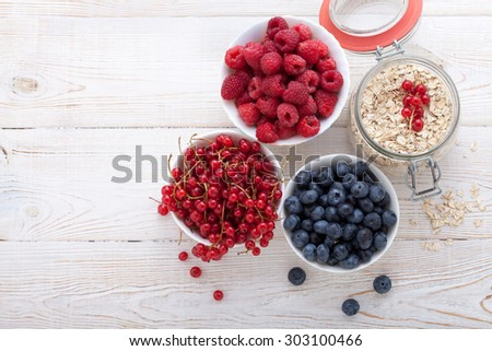 Berries, fruit, milk and muesli ingredients for healthy breakfast on white wooden table, close-up top view horizontal. Macro shot selective focus
