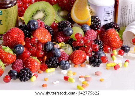 Berries, fruits, vitamins and nutritional supplements on a white background - stock photo