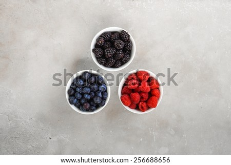 Berries in ramekins on a stone background