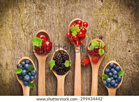 Berries in wooden spoons on wood texture - stock photo