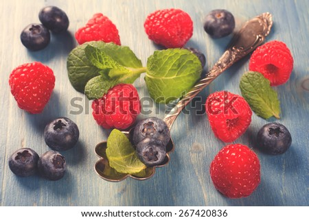 Berries on Blue Wooden Background. Summer or Spring Organic Berry over Wood. Raspberries, Blueberry, Vintage Spoon and Mint. Agriculture, Gardening, Harvest Concept. Retro style toned.  - stock photo