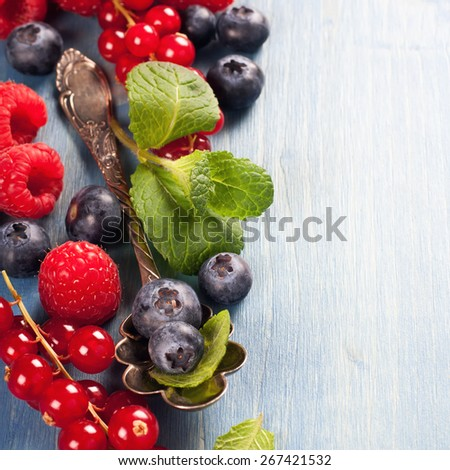 Berries on Blue Wooden Background. Summer or Spring Organic Berry over Wood. Raspberries, Blueberry, Vintage Spoon and Mint. Agriculture, Gardening, Harvest Concept. Copy space. - stock photo