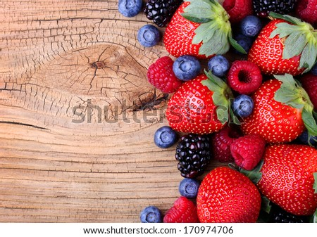 Berries on Wooden Background. Strawberries, Blueberry, Raspberries, and Blackberry. - stock photo