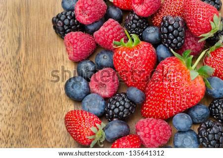 berries on wooden background (strawberries, raspberries, blackberries, blueberries) horizontal - stock photo